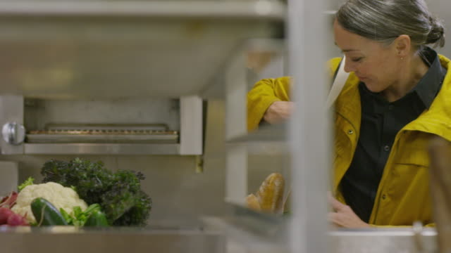Handheld shot of female chef with crate of vegetables entering into commercial kitchen