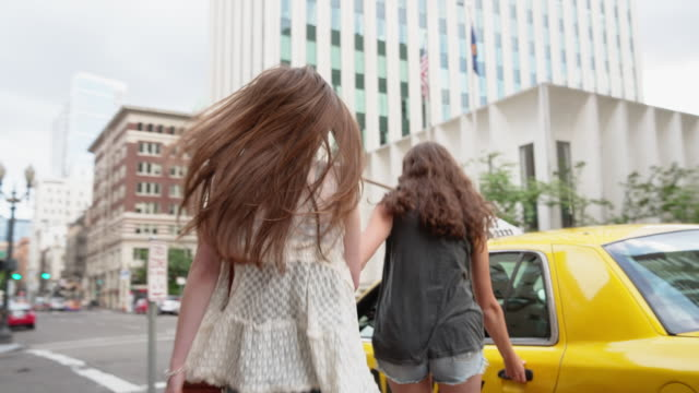 handheld shot of female friends getting into taxi at city street - yellow taxi stock videos & royalty-free footage