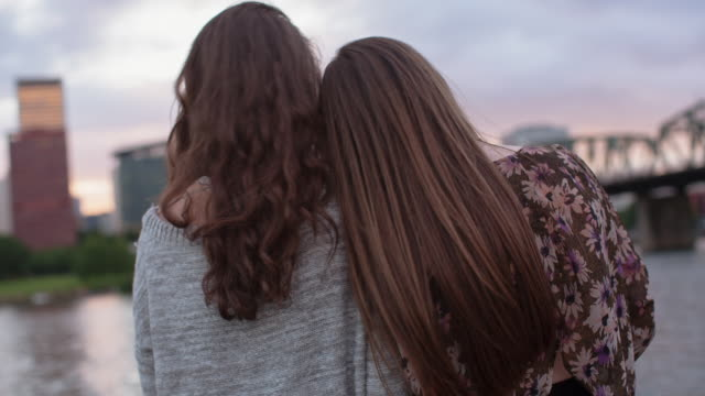 Handheld shot of female friends looking at view while standing by Willamette River during sunset