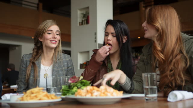 Handheld shot of female friends talking while having food at table in restaurant