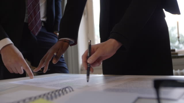 vidéos et rushes de handheld shot of female lawyer discussing over document with colleagues at table during meeting in legal office - politique