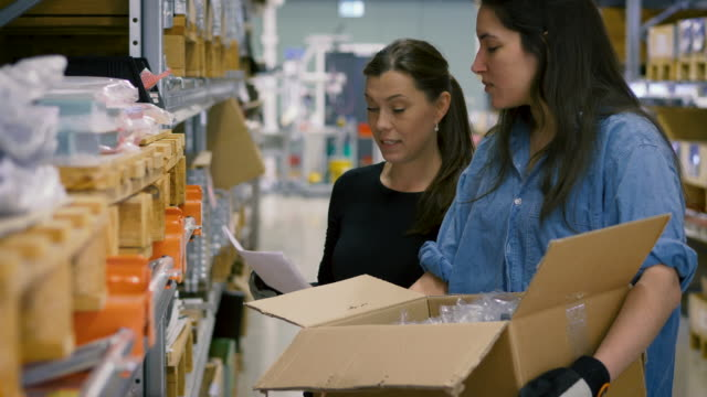 Handheld shot of female mature worker explaining checklist to young colleague while looking at boxes on rack in warehouse