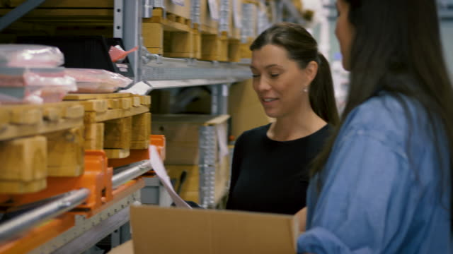 Handheld shot of female mature worker with checklist discussing with colleague over boxes on rack
