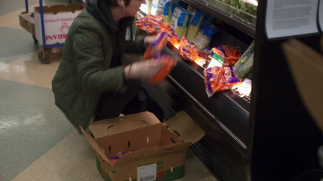 Handheld shot of female worker arranging food products in refrigerated section