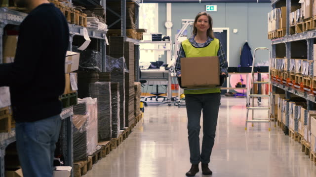Handheld shot of female worker holding box and walking while greeting colleagues in warehouse