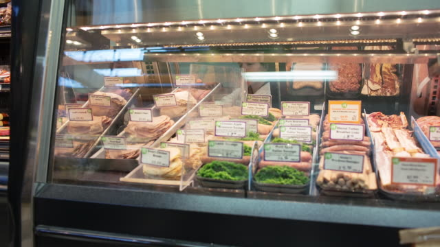 handheld shot of female worker keeping various meats in refrigerated section at store - 肉点の映像素材/bロール