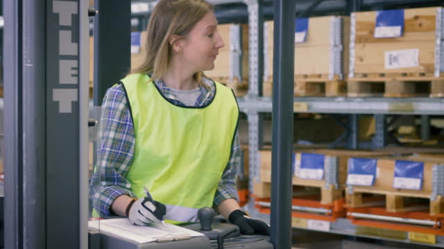 handheld shot of female worker showing checklist to male coworker in warehouse - manufacturing occupation stock videos & royalty-free footage