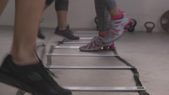 vidéos et rushes de handheld shot of females using agility ladder in gym - quête de beauté