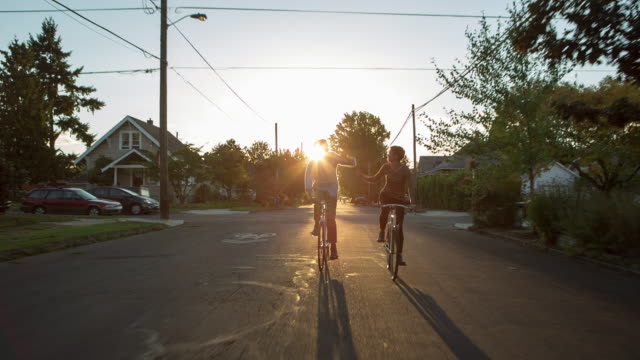 handheld shot of friends doing high-five while cycling on road - portland oregon bike stock videos & royalty-free footage