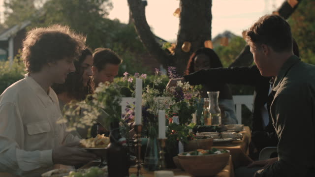 Handheld shot of friends enjoying by table at garden party
