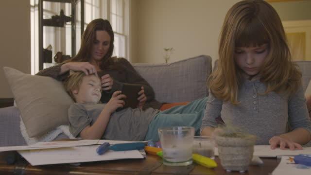handheld shot of girl drawing on paper while family relaxing on sofa in living room - 8 9 år bildbanksvideor och videomaterial från bakom kulisserna