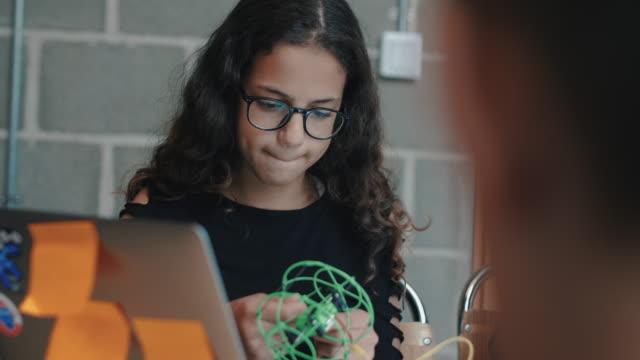 vídeos y material grabado en eventos de stock de handheld shot of girl making drone while sitting by friend in workshop - robótica