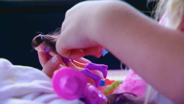 Handheld shot of girl riding in car, brushing doll's hair, slow motion