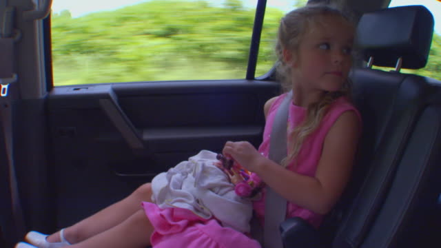 Handheld shot of girl riding in car, looks backward and smiles, slow motion