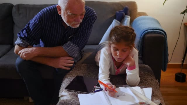 Handheld shot of grandfather talking to granddaughter doing homework on sofa in living room at home
