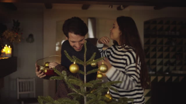 handheld shot of happy couple enjoying while decorating christmas tree with baubles at home - 談笑する点の映像素材/bロール