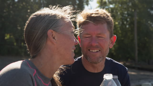 vídeos y material grabado en eventos de stock de handheld shot of happy couple toasting water bottles while sitting at riverbank - barba de tres días