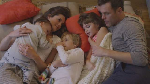 stockvideo's en b-roll-footage met handheld shot of happy family talking while relaxing on carpet at home - familie met drie kinderen