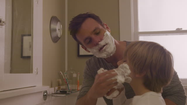 handheld shot of happy father assisting son in applying shaving cream on face at bathroom - 鏡点の映像素材/bロール