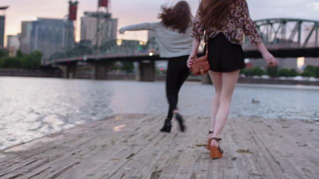 Handheld shot of happy female friends enjoying on pier over Willamette River in city during sunset