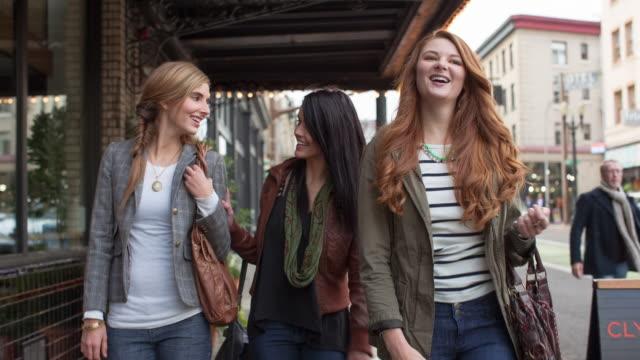 handheld shot of happy female friends talking while walking on sidewalk - punto di vista frontale video stock e b–roll