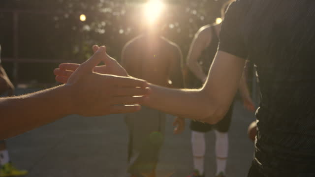 handheld shot of happy friends greeting at basketball court during sunset - macchina da presa manuale video stock e b–roll