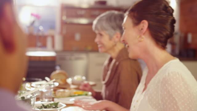 vídeos de stock, filmes e b-roll de handheld shot of happy friends talking while sitting at dining table - sala de jantar