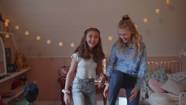 handheld shot of happy girl dancing with friend in bedroom at home - filming stock videos & royalty-free footage