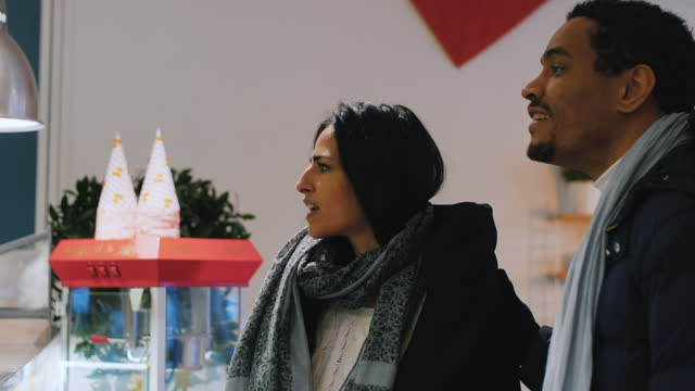 handheld shot of happy mid adult couple talking and walking in store - mid adult couple stock videos & royalty-free footage
