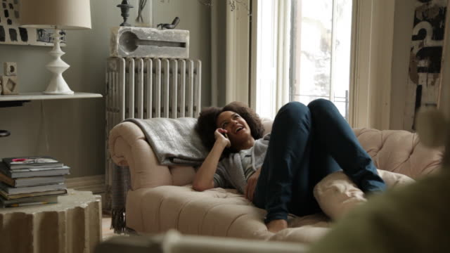 handheld shot of happy woman talking on smart phone while relaxing at home - heizung stock-videos und b-roll-filmmaterial