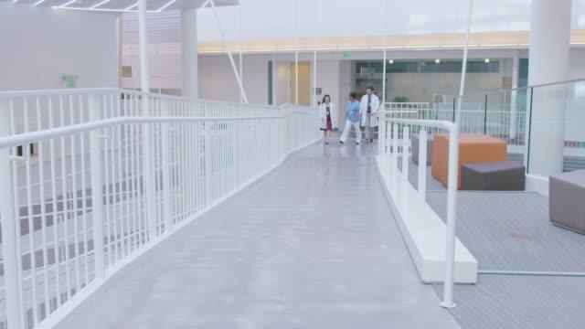 handheld shot of healthcare coworkers discussing while walking in hospital corridor - skakig kamerabild bildbanksvideor och videomaterial från bakom kulisserna