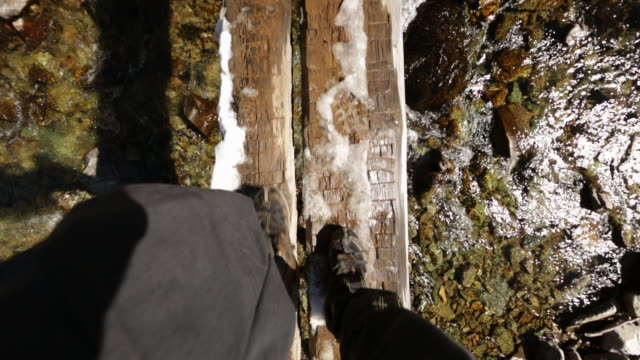 Handheld shot of hiker crossing snowy footbridge over river in forest