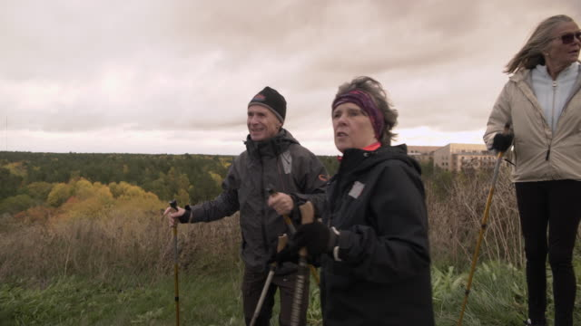Handheld shot of hikers exploring while Nordic walking on mountain against sky