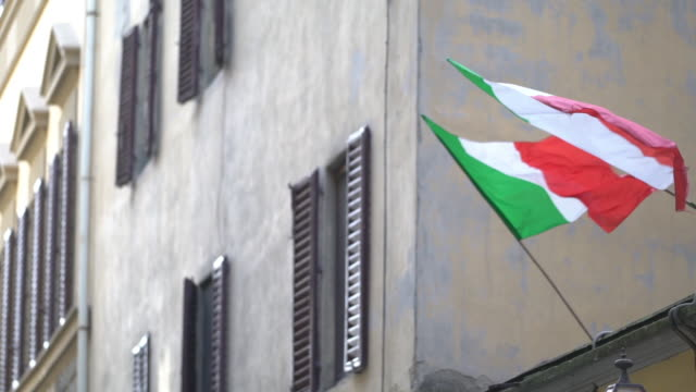 handheld shot of italian flags waving against building in city - italienische flagge stock-videos und b-roll-filmmaterial