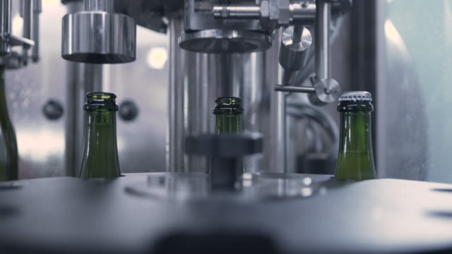 handheld shot of machinery fitting caps to filled beer bottles at brewery - 手提 個影片檔及 b 捲影像