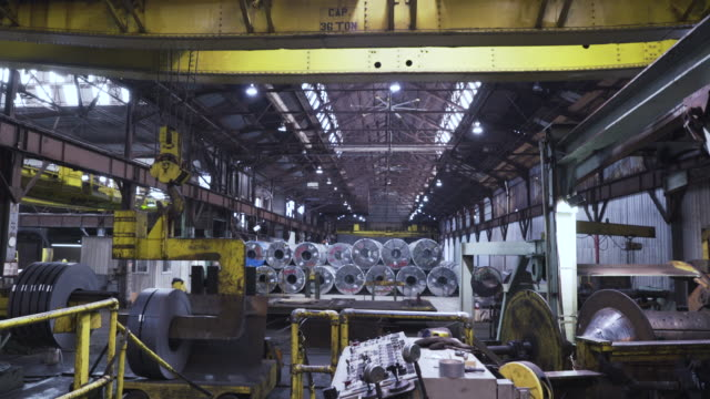 Handheld shot of machinery lifting metal at factory