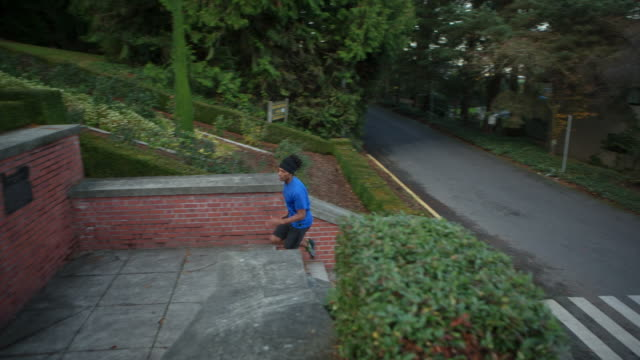 handheld shot of male athlete moving up on steps at park - kosmetisches stirnband stock-videos und b-roll-filmmaterial