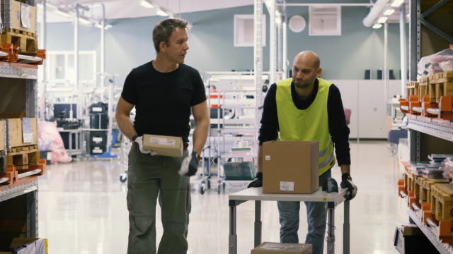 Handheld shot of male colleagues with boxes talking while walking in aisle at warehouse