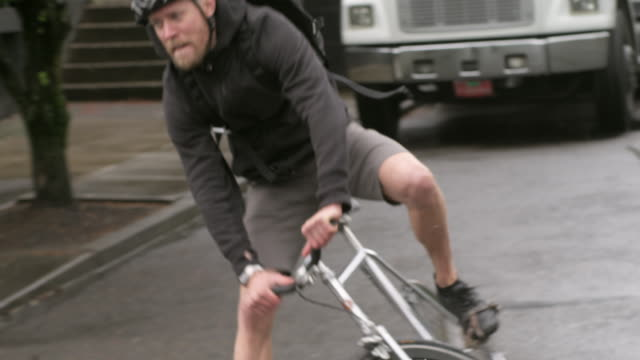 handheld shot of male commuter riding bicycle falls off on street - sporthjälm bildbanksvideor och videomaterial från bakom kulisserna