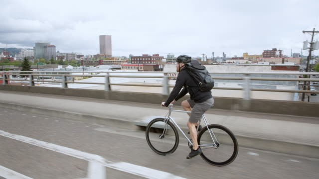 handheld shot of male commuter riding bicycle on bridge in city against cloudy sky - portland oregon bike stock videos & royalty-free footage
