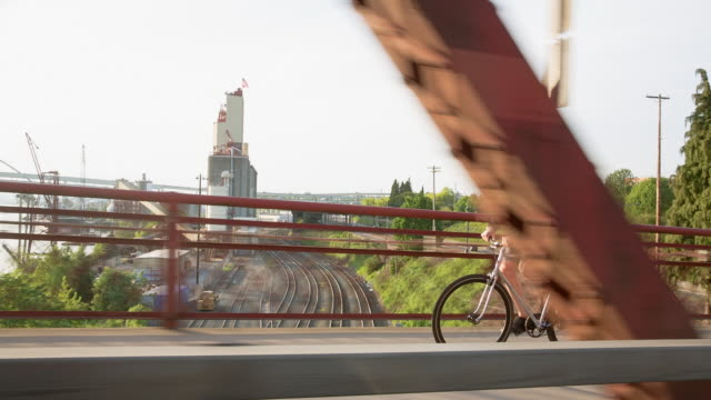 handheld shot of male commuter riding bicycle on bridge over railroad tracks and sea against clear sky - portland oregon bike stock videos & royalty-free footage