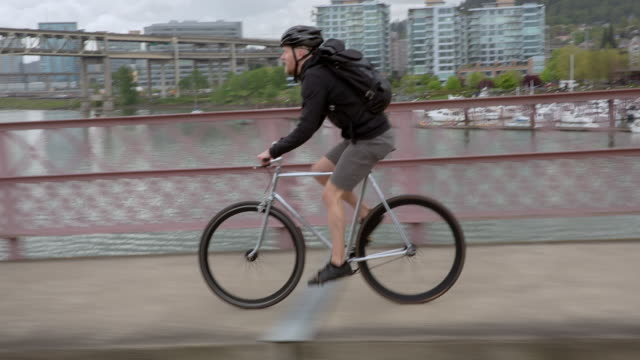 handheld shot of male commuter riding bicycle on bridge over river in city against cloudy sky - portland oregon stock videos & royalty-free footage