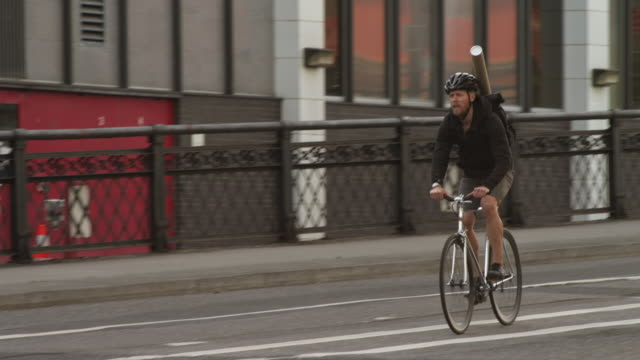 handheld shot of male commuter riding bicycle on road amidst buildings in city - portland oregon bike stock videos & royalty-free footage