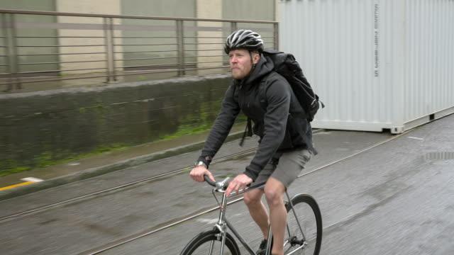 handheld shot of male commuter riding bicycle on wet street during rainy season - portland oregon bike stock videos & royalty-free footage