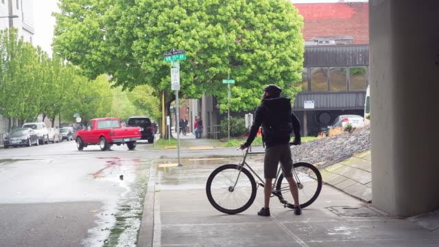 handheld shot of male commuter with bicycle standing below bridge during rainy season - portland oregon bike stock videos & royalty-free footage