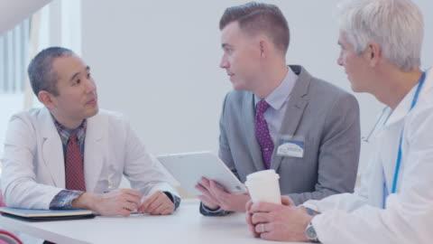 vídeos y material grabado en eventos de stock de handheld shot of male doctor with tablet computer explaining to coworkers in hospital cafeteria - vestirse formal