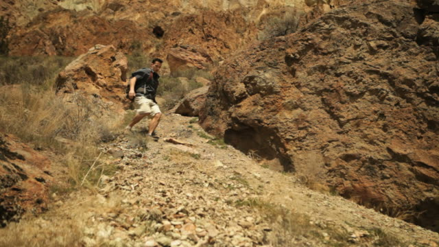 Handheld shot of male hiker moving down mountain during vacation
