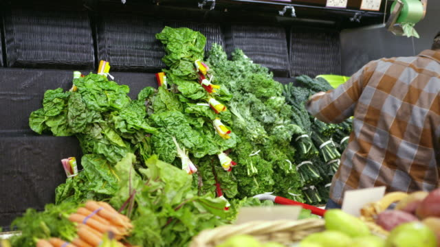 Handheld shot of male worker arranging vegetables on retail display at supermarket
