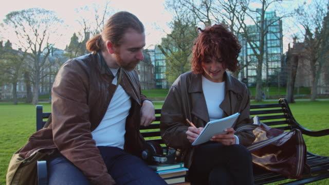 vidéos et rushes de ordinateur de poche coup d'homme et femme étudient ensemble dans le parc - écosse