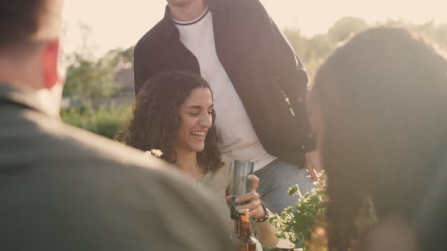 Handheld shot of man giving beer bottle to female friends at social gathering